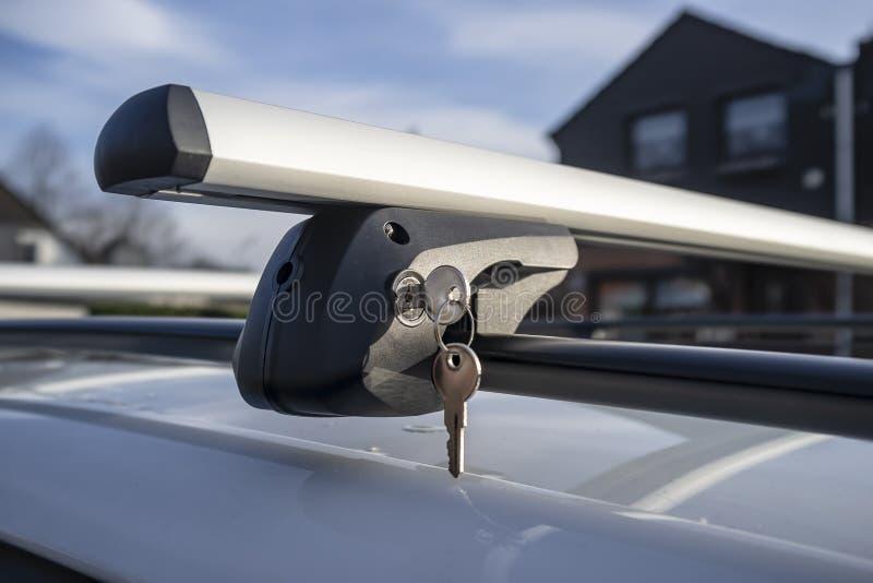 在锁的钥匙紧固车厢或货物箱子的持有人到车屋顶,在一个晴朗的春日反对天空蔚蓝 免版税图库摄影