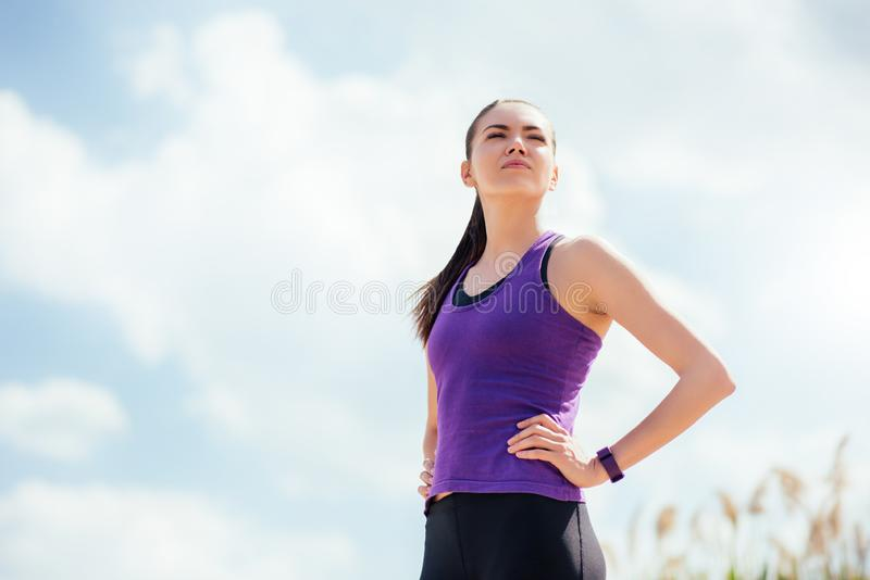 在锻炼和赛跑前后的站立的运动的年轻美女 集中于在天空背景的锻炼 库存图片