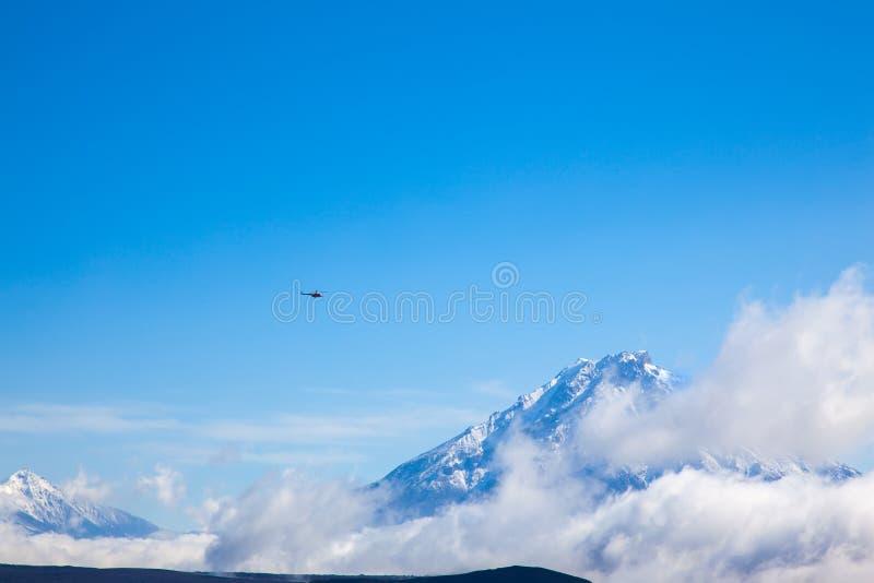 在backround天空蔚蓝的helicoper在降雪的山 火山扎尔巴奇克火山 K 库存照片