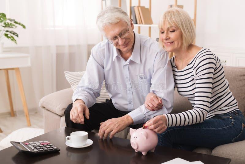 在piggybank的年长夫妇攒钱在家 免版税库存照片