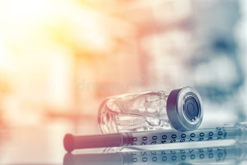 医学小瓶特写镜头或流感、麻疹疫苗瓶有注射器的和针免疫的在葡萄酒医疗背景, 免版税库存图片