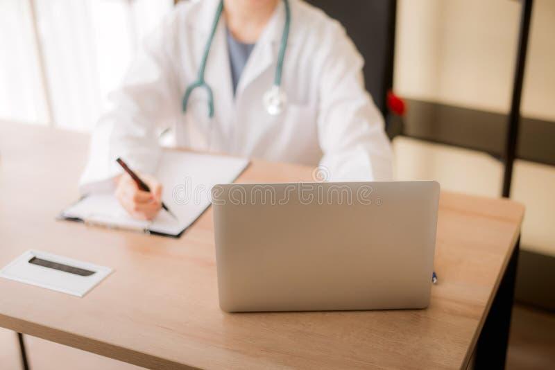 医生亚裔妇女迷离和工作坐书桌使用膝上型计算机和写笔记在医院,女性键入的在手提电脑 免版税库存照片