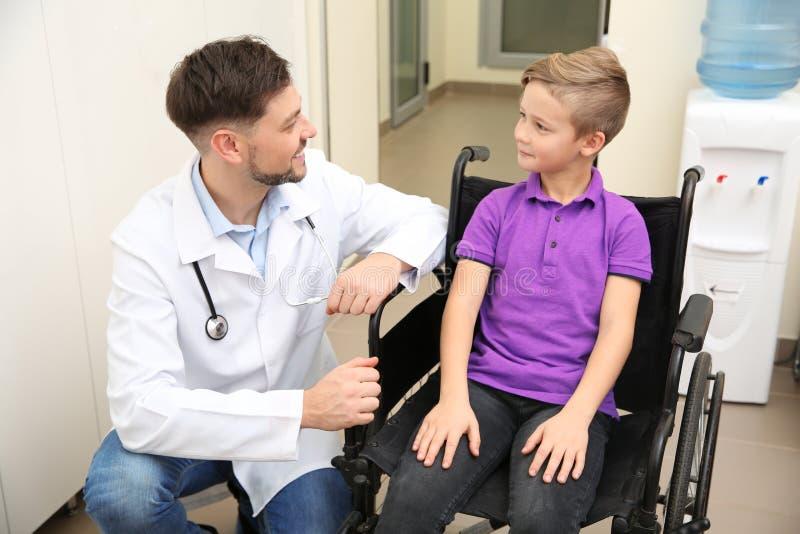 医生和小孩轮椅的 免版税库存照片