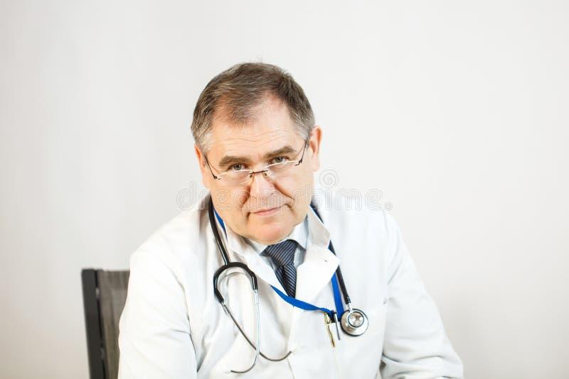 医生调查他的眼睛,严肃的神色,一个听诊器在他的脖子上 图库摄影