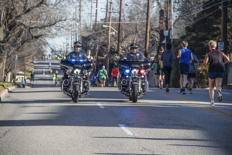 土尔沙美国3 - 16 - 2019两个有飞行闪动主导的慢跑者的摩托车警察在都市街道下在每年圣帕特里克' 免版税库存图片