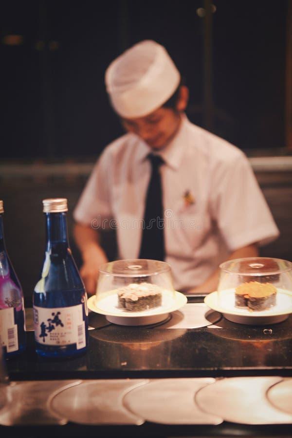 北京,中国- 2018年6月11日:中国厨师烹调在餐馆访客前面的寿司 库存照片