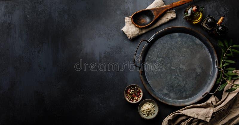 圆的金属盘子和香料在黑暗的具体背景表面拷贝空间 库存图片