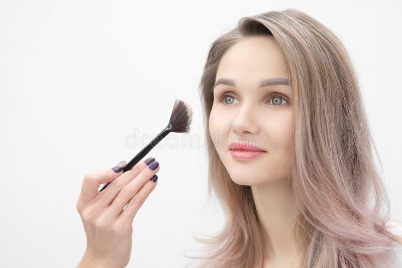 化妆师在白色背景做构成美丽的白肤金发的女孩 有刷子和面孔的特写镜头手 库存照片