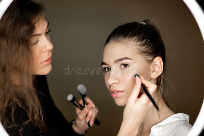 化妆师迷人的女孩对构成做一美丽的少女 库存图片