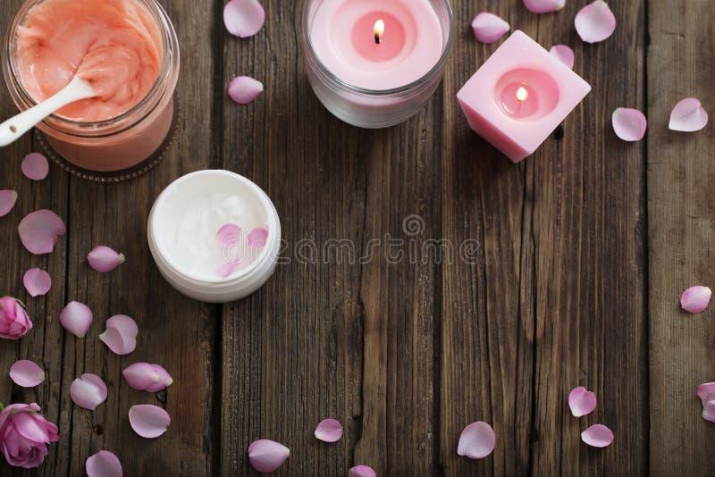 化妆面具和燃烧的蜡烛在老木背景 免版税库存照片