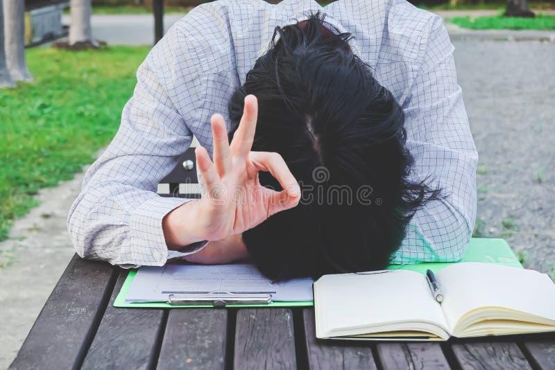 劳累过度,疲乏的商人在办公室睡觉在他书写工作的在书,在他整天后工作,但是他显示的ok姿态 库存照片