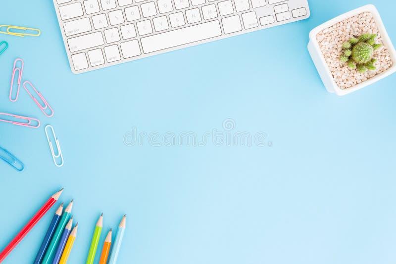 办公桌平的被放置的照片有铅笔和键盘的,在蓝色背景的顶视图workpace和拷贝空间 免版税图库摄影