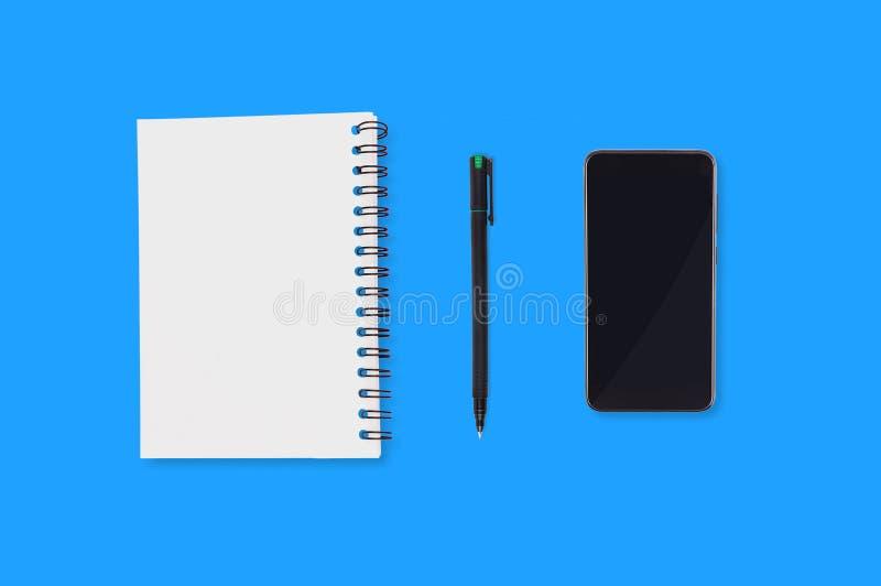 办公用品与空白纸塑料笔和黑智能手机的纸笔记薄在蓝色桌上延长 顶视图 企业conce 免版税库存照片