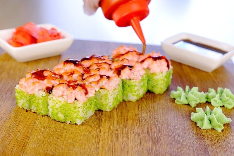 厨师在有有山葵、姜和大豆sause的木板倾吐卷用调味汁并且服务他们 免版税库存图片