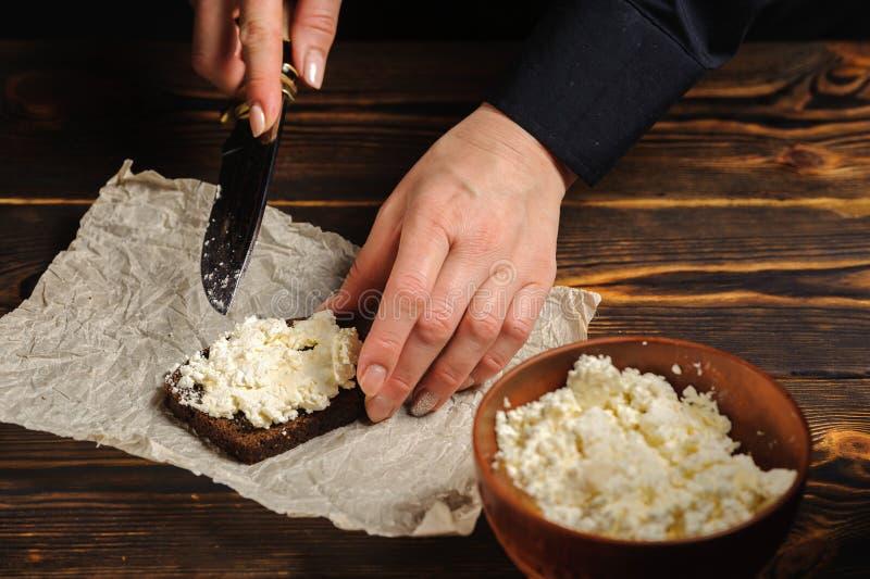 厨师涂在面包的酸奶干酪 图库摄影