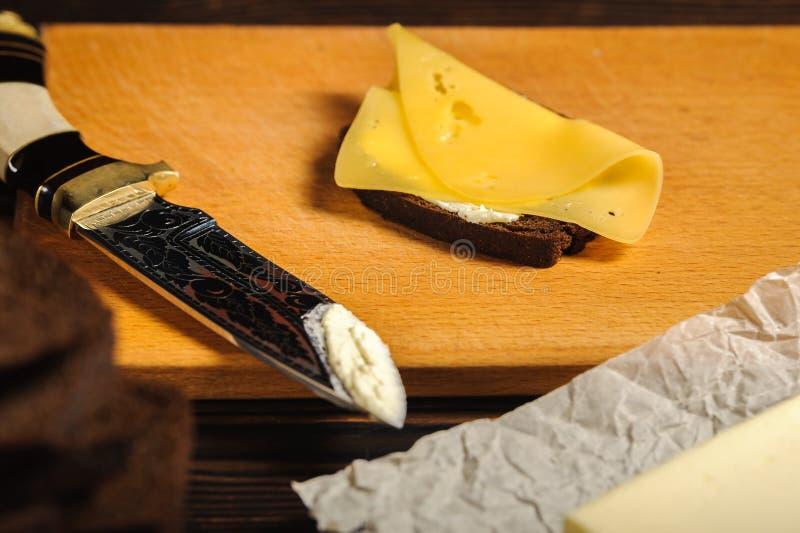 厨师由面包和乳酪做一个三明治 免版税库存图片