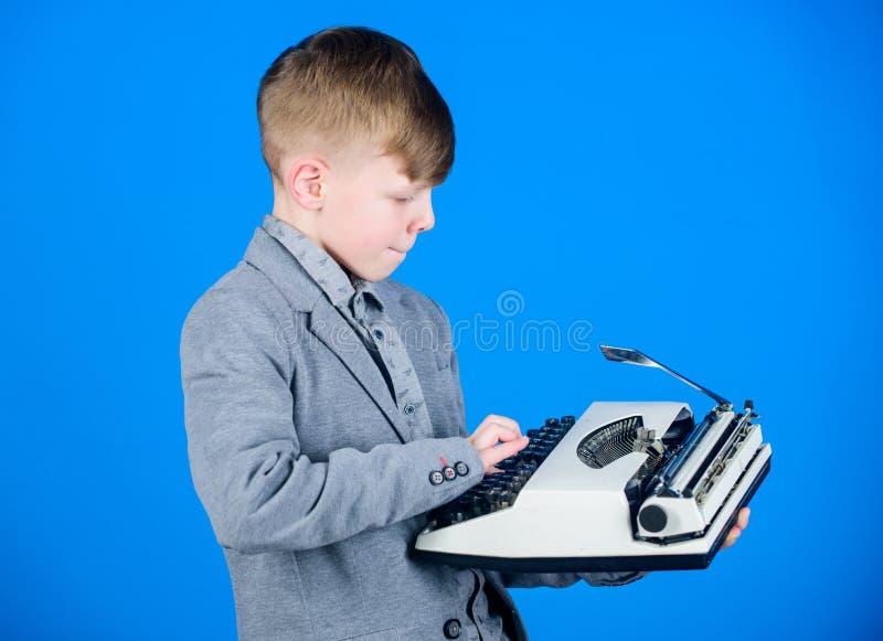 去的Hes写构成 聪明的儿童作家 一点键入在减速火箭的打字机的作家 逗人喜爱男孩作家工作 免版税库存图片
