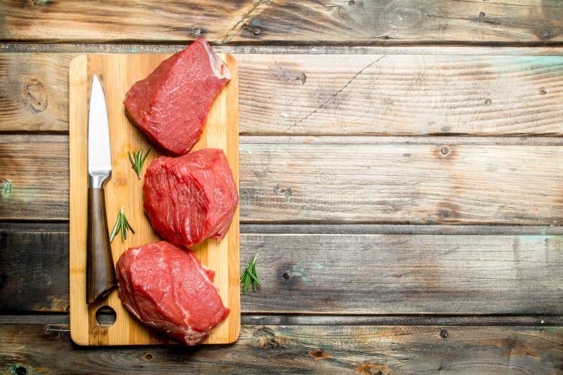 原始的肉 牛肉片断与刀子的 库存照片
