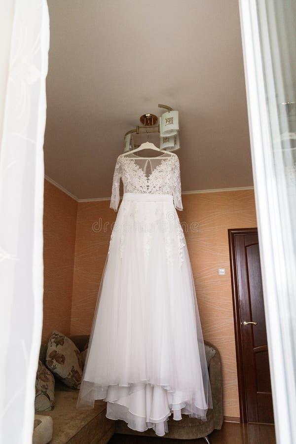 垂悬在枝形吊灯的新娘的美丽的婚纱在屋子里 免版税库存图片