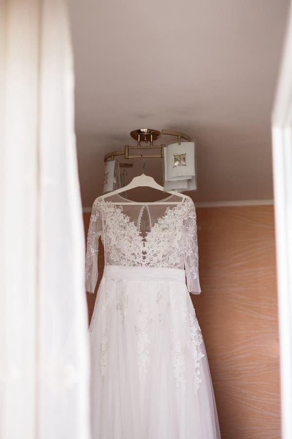垂悬在枝形吊灯的新娘的美丽的婚纱在屋子里 免版税图库摄影