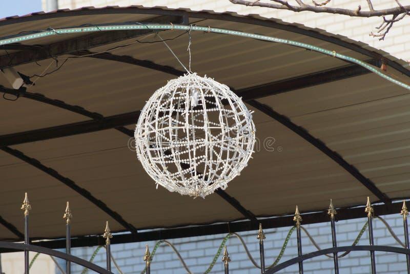 垂悬在灰色篱芭的街道上的圆的白色装饰灯笼 库存照片