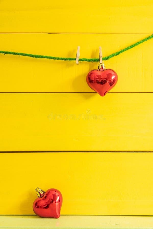 垂悬在绿色绳索在地板上的一红心另一红心下落在黄色木背景 库存图片