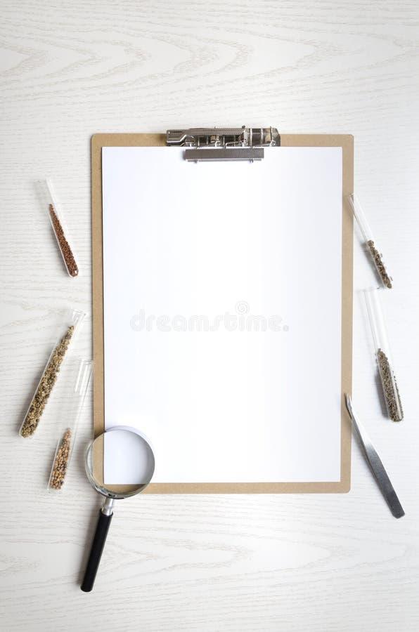 垂直的射击 有白纸和试管的剪贴板有种子,在白色桌上的放大镜不同形式的  la的概念 库存图片