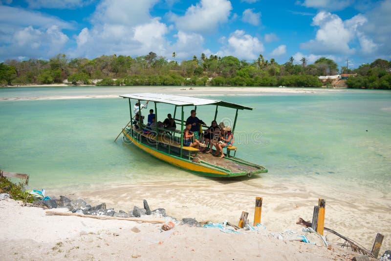 到达Sossego海滩Ilha de Itamaraca,巴西的小船的人们 库存照片