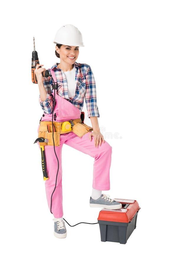 制服藏品工具箱和钻子的女性建筑工人 免版税库存照片