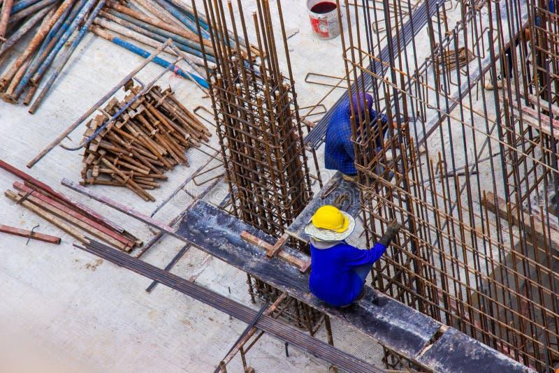 制造大铁棍增强酒吧的建筑工人在建筑区域建筑工地 库存照片