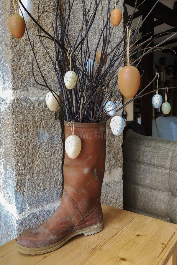 分支用在一双胶靴的装饰鸡蛋 免版税库存照片