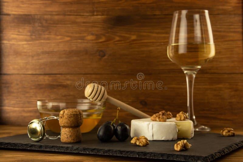 切好的软制乳酪乳酪、坚果、蜂蜜、甜葡萄和黄柏从酒瓶在一杯的背景白色干萄酒 库存图片