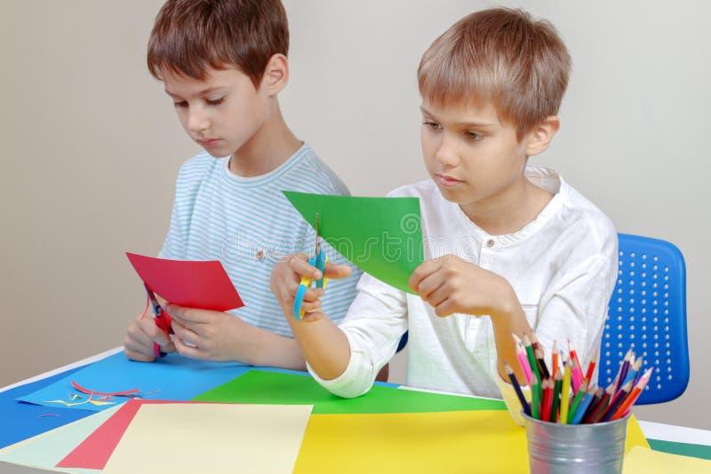 切开与剪刀的孩子彩纸在桌上 图库摄影