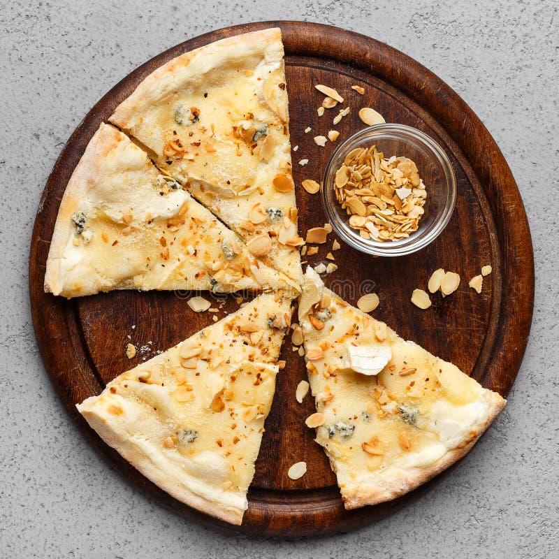 切片四在木板的奶酪披萨 库存照片