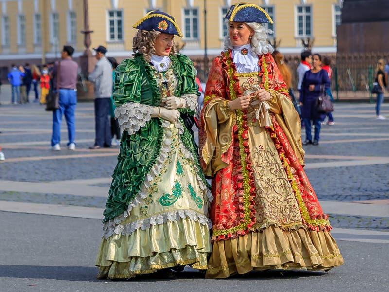 周期性服装的女性艺人等候游人的由宫殿正方形的圣彼德堡,俄罗斯偏僻寺院冬宫 免版税图库摄影