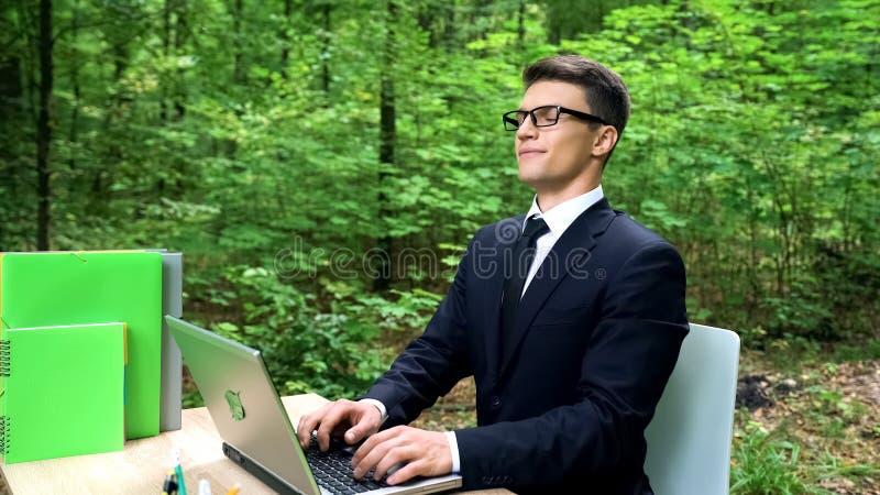 呼吸新鲜空气的商人在环境友好的办公室,坐在书桌在公园 库存图片