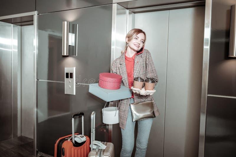 告诉繁忙的女实业家她的等待他的男朋友在电梯附近 免版税库存图片