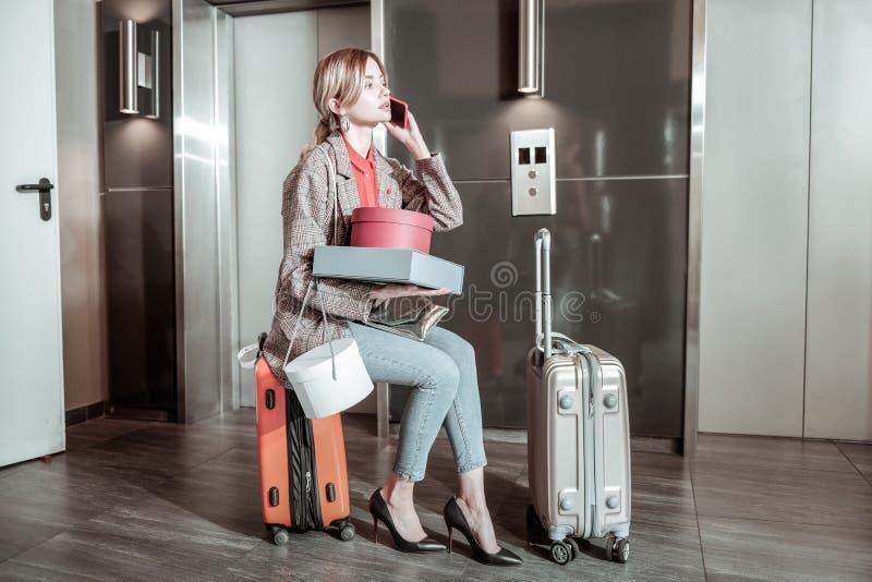 告诉繁忙的妻子坐手提箱和她的丈夫,当等待时 免版税库存图片