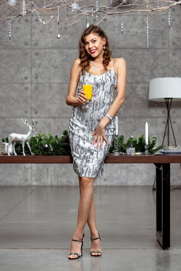 Ładna brunetki dziewczyna trzyma szkło sok w olśniewającej szarej wieczór sukni stoi obok stołu z Nowym zdjęcie stock