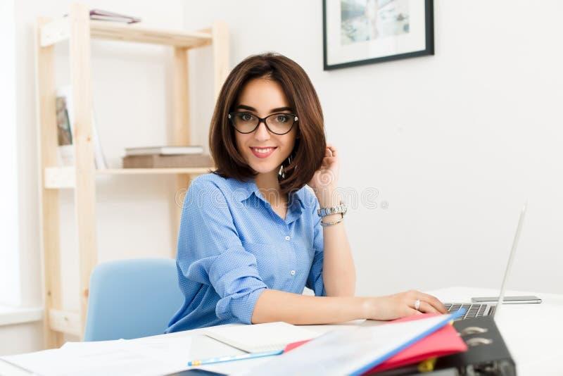 Ładna brunetki dziewczyna w błękitnej koszula siedzi przy stołem w biurze Pracuje z laptopem i ono uśmiecha się ślicznymi th zdjęcia stock