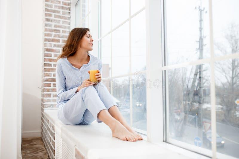 Ładna brunetki dziewczyna w bławej piżamie siedzi na windowsill i trzyma szkło świeży sok w ona ręki obraz stock
