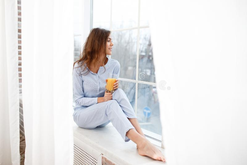 Ładna brunetki dziewczyna w bławej piżamie siedzi na windowsill i trzyma szkło świeży sok w ona ręki zdjęcia stock