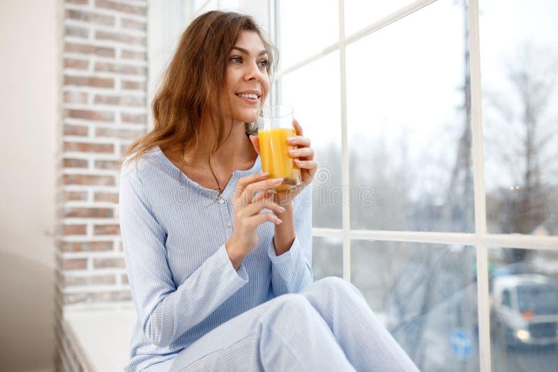 Ładna brunetki dziewczyna w bławej piżamie siedzi na windowsill i trzyma szkło świeży sok w ona ręki fotografia stock