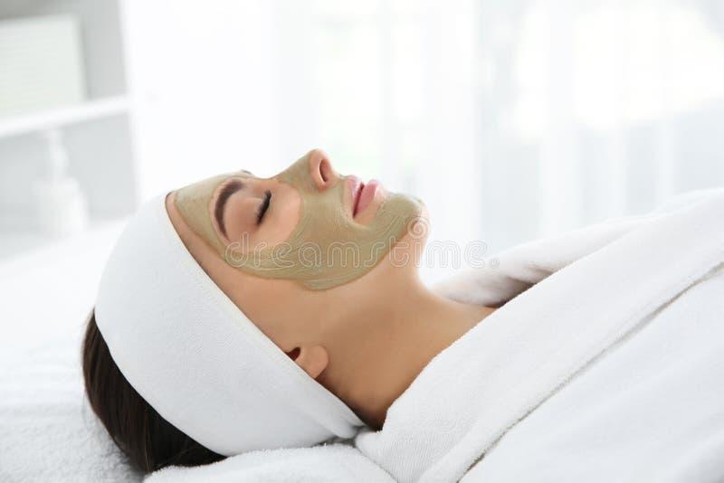 Ładna kobieta z gliny maską na jej twarzy fotografia stock