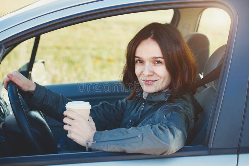 Ładna młoda uśmiechnięta kobieta jedzie samochód i pije kawę obrazy royalty free