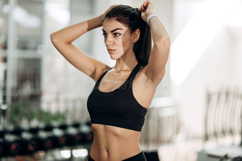 Ładna szczupła dziewczyna ubierająca w czarnym sportswear jest w gym wiąże jej włosy obrazy stock