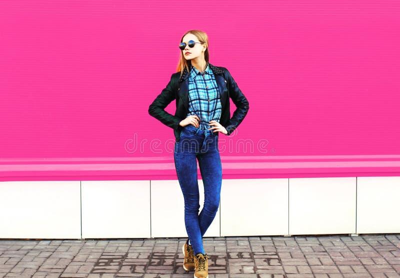 Ładny blondynki dziewczyny model w długiej pozuje jest ubranym rockowej czerń stylu kurtce, kapelusz na miasto ulicie nad kolorow fotografia royalty free