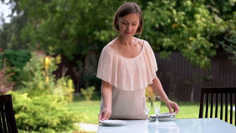 Ładny gospodyni domowej porcji stół, czekanie dzieciaki i mąż dla gościa restauracji outdoors, obrazy royalty free