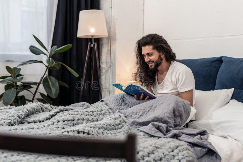 Ładny radosny mężczyzny obsiadanie na łóżku obraz stock