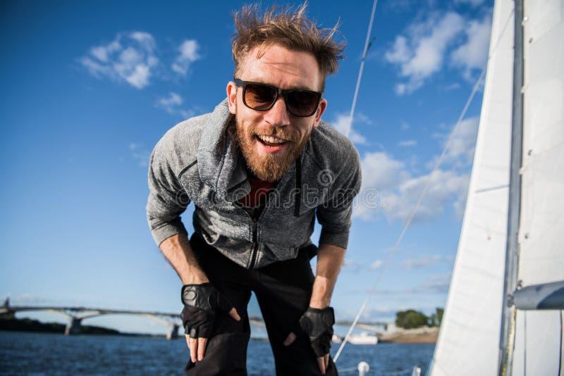 Ładny szczęśliwy brodaty mężczyzny żeglarz thumbing w górę i przejawia positivity podczas gdy morzu lub rzece przy jego łodzią na fotografia royalty free